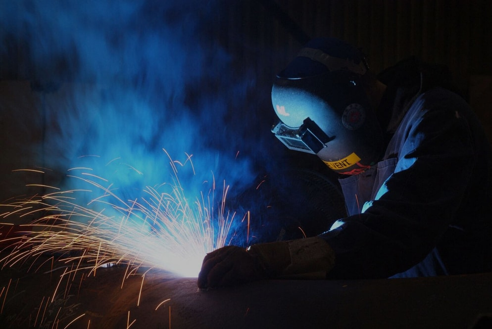 A welder working on a single step handrail